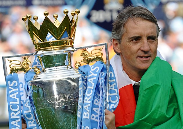 Manchester City's Italian Manager Roberto Mancini Celebrate With The Premier League Trophy On The Pitch 