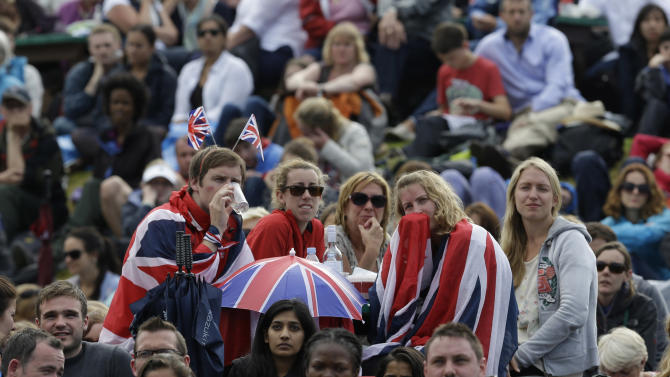 Spectators watch Andy Murray of Britain play Roger Federer of Switzerland during the men's singles final match at the All England Lawn Tennis Championships at Wimbledon, England, Sunday, July 8, 2012. (AP Photo/Alastair Grant)