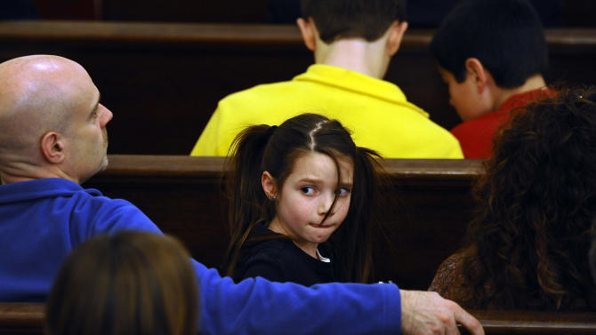 A girl sits with her family in a pew during an interfaith a sermon at Newtown Congregational Church in Newtown, Conn., Sunday, Jan. 20, 2013.  The Rev. James A. Forbes, Jr., who led one of the country's most prominent liberal Protestant churches, is speaking at the church to honor the victims of last month's school shooting and the legacy of the Rev. Martin Luther King Jr. (AP Photo/Jessica Hill)