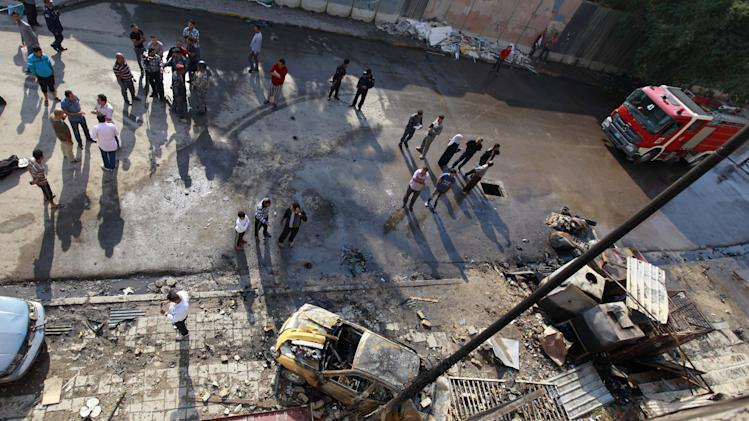 People gather at the scene of a car bomb attack in central Baghdad, Iraq, Wednesday, Nov. 14, 2012. Iraqi insurgents unleashed a new wave of bombings across the country early Wednesday targeting security forces and civilians, killing and wounding scores of people, police said. (AP Photo/Khalid Mohammed)