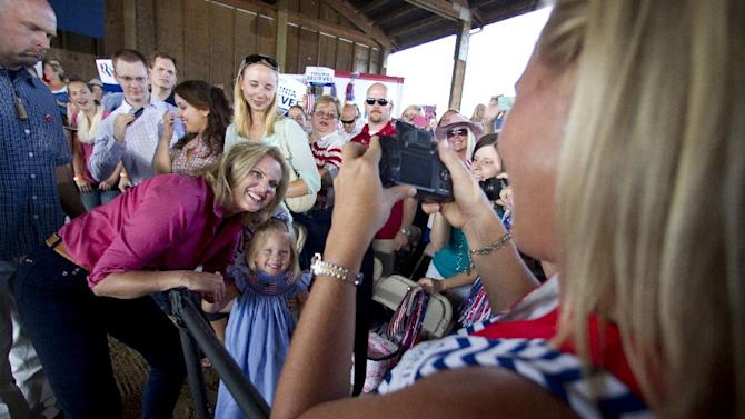 Ann Romney, wife of Republican presidential candidate, former Massachusetts Gov. Mitt Romney, poses with four-year-old Caroline Grinstead, as her mother Shannon Grinstead, right, of Ashburn, Va., takes photos as Mrs. Romney greeted the crowd of supporters during a Women for Mitt rally in Leesburg, Va., Friday, Sept. 7, 2012.  (AP Photo/Manuel Balce Ceneta)