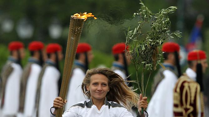 A torchbearer runs with the Olympic flame during a ceremony at Panathenaean stadium in Athens, Thursday, May 17, 2012. The torch begins its 70-day journey to arrive at the opening ceremony of the London 2012 Olympics, from the Greek capital, to cover about 8,000-mile (12,875-kilometer) on its progress over many parts of England to start the games. (AP Photo/Thanassis Stavrakis)