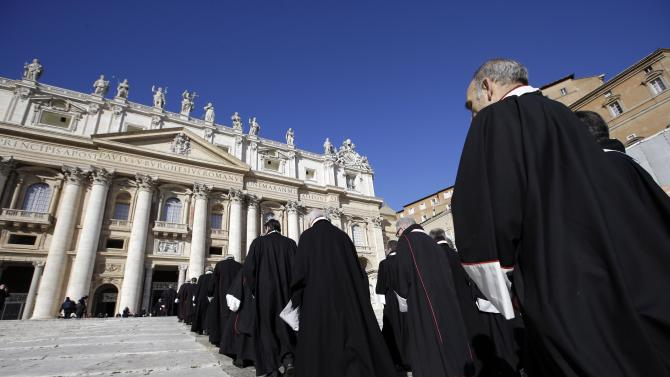 Members of the Knights of Malta walk in procession towards St. Peter's Basilica during a celebration to mark the 900th anniversary of the Order of the Knights of Malta, at the Vatican Saturday, Feb. 9, 2013. The order traces its history to the 11th century with the establishment of an infirmary in Jerusalem that cared for people of all faiths making pilgrimages to the Holy Land. It is the last of the great lay chivalrous military orders like the Knights Templars that combined religious fervor with fierce military might to protect and expand Christendom from Islam's advance during the Crusades. In February 1113, Pope Paschal II issued a papal bull recognizing the order as independent from bishops or secular authorities, reason for Saturday's anniversary celebrations at the Vatican. (AP Photo/Gregorio Borgia)