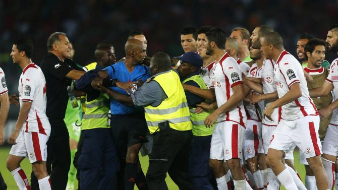 Tunisia players confront the referee Rajindraparsad Seechurn after losing their quarter-final soccer match of the 2015 African Cup of Nations against Equatorial Guinea in Bata