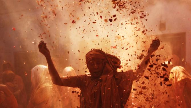 Widow daubed in colours dances as she takes part in Holi celebrations at Vrindavan
