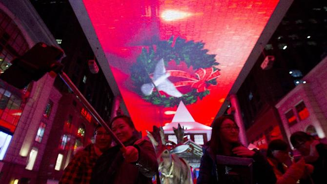 Shoppers pose for selfies near Christmas decorations at a shopping mall in Beijing, China, Thursday, Dec. 25, 2014. (AP Photo/Ng Han Guan)