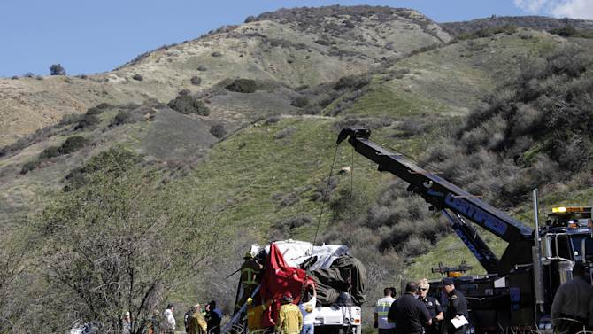 A heavy-duty tow truck lifts a tour bus back onto the road Monday, Feb. 4, 2013, after it collided with two other vehicles and crashed Sunday, killing at least eight people and injuring 38, on Highway 38 just north of Yucaipa, Calif.  The bus was carrying a tour group from Tijuana, Mexico.  (AP Photo/Reed Saxon)