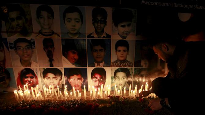 File photo of a man placing rose after lighting candles in front of portraits of victims of the Taliban attack on Army Public School in Peshawar, during a candlelight vigil in Lahore