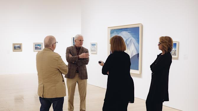 """In this Wed., Oct. 7, 2015, photo, Steve Martin, second from left, conducts an exhibition walk through along with co-curators, Andrew Hunter, left, Cynthia Burlingham, center, and Ann Philbin, Director of The Hammer Museum, for the exhibition """"The Idea of North: The Paintings of Lawren Harris,"""" at The Hammer Museum in in Los Angeles. The show opens Sunday, Oct. 11, 2015. (Photo by Casey Curry/Invision/AP)"""