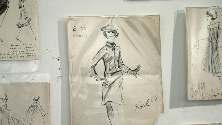 In this Monday, Dec. 30, 2013 photo, one of the few signed drawings that Karl Lagerfeld did, hang on the wall of the Modern Auction house in West Palm Beach, Fla. Most in-house designers are not allowed to sign their work. A 50-year-old archive of some of Karl Lagerfeld's early fashion designs is going up for auction in Florida. In the 1960s, Lagerfeld was designing for Elizabeth Taylor and other celebrities while working for the House of Tiziani in Rome. (AP Photo/J Pat Carter)