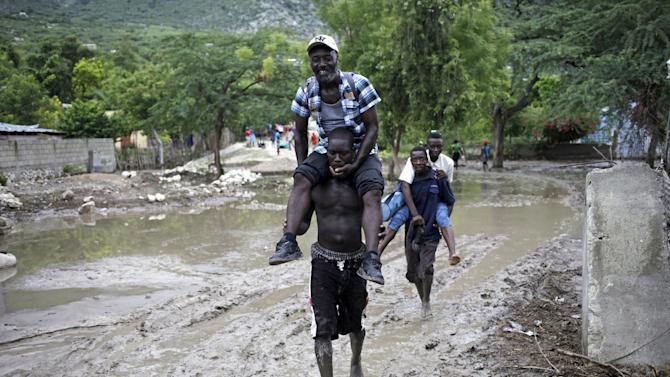 Men carry others, so they do not soil their shoes and clothes, through a mudslide caused by Tropical Storm Erika in Carries