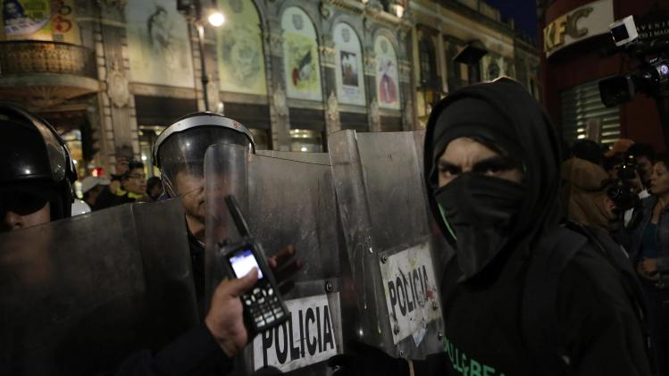 Riot policemen block demonstrators from entering Zocalo Square, during a march against the radical reform of the country's energy market in downtown Mexico City