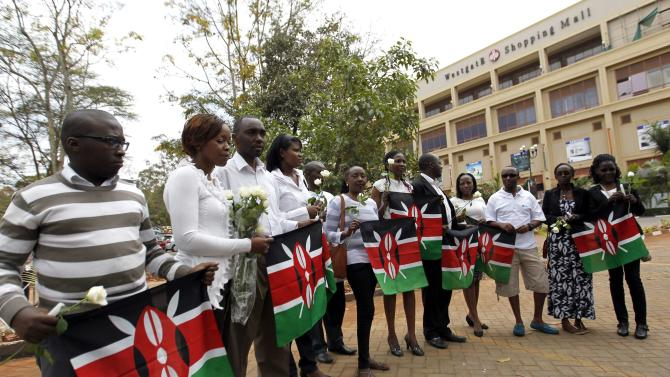 Survivors and relatives of victims carry Kenyan national flags as they attend the first anniversary memorial service of the Westgate shopping mall terrorist attack in Nairobi
