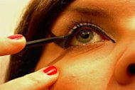 Applying eye makeup.