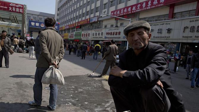 """A man squats on a concrete barrier as others wash and scrub the site of the Wednesday explosion outside the Urumqi South Railway Station in Urumqi in northwest China's Xinjiang Uygur Autonomous Region on Thursday, May 1, 2014. Chinese President Xi Jinping demanded """"decisive"""" action against terrorism after a slashing and bomb attack at a Xinjiang train station killed three people and injured 79 while the leader was wrapping up a tour of the far-western region.(AP Photo/Ng Han Guan)"""