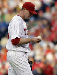 FILE - In this May 22, 2012, file photo, Philadelphia Phillies' Roy Halladay looks over a ball during a baseball game against the Washington Nationals in Philadelphia. Halladay has been put on the disabled list because of a strained right shoulder and is expected to be out of the rotation for six to eight weeks, Phillies assistant general manager Scott Proefrock said, Tuesday, May 29, 2012. (AP Photo/Matt Slocum, File)