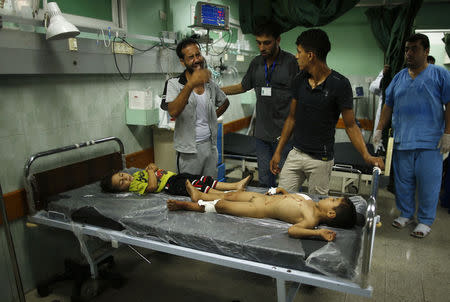 A Palestinian man cries as he stands next to two boys at a hospital in the northern Gaza Strip