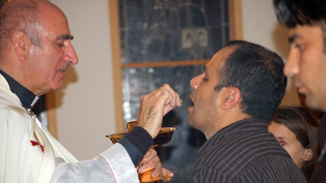 This Nov. 7, 2011 photo shows George Saade, 39, of Albuquerque, N.M. taking Communion at a mass in Arabic at Our Lady of Perpetual Help Byzantine Catholic Church in Albuquerque. Archdiocese of Santa Fe officials believe the Catholic Mass in Arabic was the first in New Mexico's history. (AP Photo/Russell Contreras)