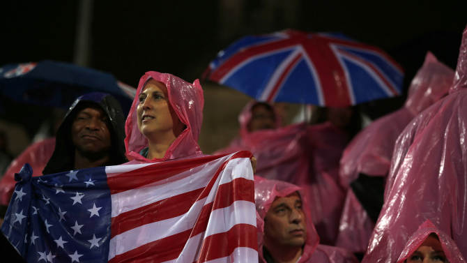 Fans of the U.S. shelter from the rain as they watch the women's beach volleyball semifinal match between Ross and Kessy of the U.S. and Brazil's Juliana and Larissa at Horse Guards Parade during the London 2012 Olympic Games