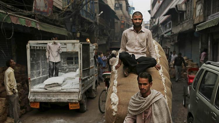 An Indian man rides on top of sacks of food on a bicycle rickshaw at a market in New Delhi, India, Tuesday, Oct. 30, 2012. India's central bank left its key interest rate unchanged Tuesday but trimmed the cash reserve ratio, resisting growing pressure from New Delhi to cut rates even as it slashed its growth forecast and raised its inflation projection for Asia's third-largest economy. (AP Photo/Kevin Frayer)