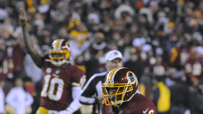 Washington Redskins quarterback Robert Griffin III (10) reacts as running back Alfred Morris (46) heads for a touchdown during the second half of an NFL football game against the Dallas Cowboys on Sunday, Dec. 30, 2012, in Landover, Md. (AP Photo/Richard Lipski)