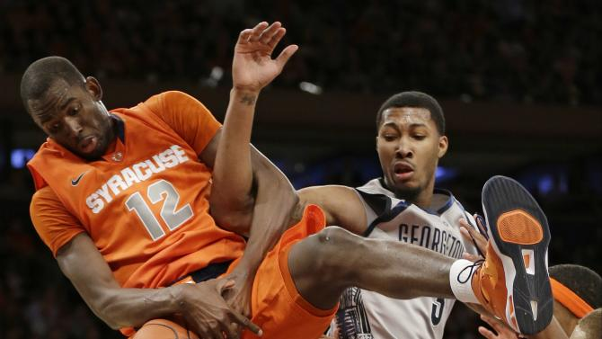 Syracuse's Baye Keita (12) and Georgetown's Mikael Hopkins (3) fight for control of the ball during the second half of an NCAA college basketball game at the Big East Conference tournament Friday, March 15, 2013, in New York. Syracuse won the game 58-55. (AP Photo/Frank Franklin II)