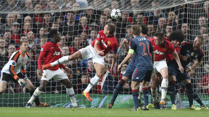 Manchester United's Nemanja Vidic, center, scores the opening goal during the Champions League quarterfinal first leg soccer match between Manchester United and Bayern Munich at Old Trafford Stadium, Manchester, England, Tuesday, April 1, 2014.(AP Photo/Jon Super)