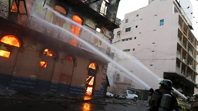 Firefighters extinguish a fire on an old building in downtown Panama City