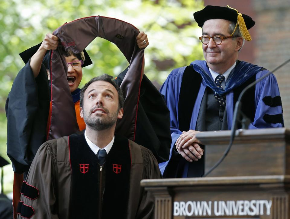 Actor and director Ben Affleck, lower left, receives an honorary degree at Brown University's commencement in Providence, R.I., Sunday, May 26, 2013. (AP Photo/Michael Dwyer)