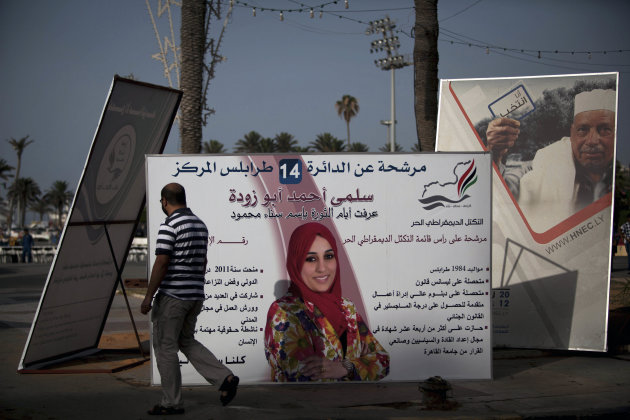 A Libyan man walks near National Assembly election campaign posters at Martyr&#39;s Square in Tripoli, Libya, Thursday, July 5, 2012. The Libyan National Assembly elections will take place on July 7, 2012, the first free elections since 1969. (AP Photo/Manu Brabo)