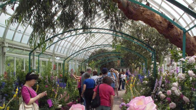 "In this May 26, 2012 photo, visitors to the New York Botanical Garden in New York walk through  ""Monet's Garden,"" which evokes the impressionist artist Claude Monet's garden at Giverny, his home in France, from 1883 until his death in 1926. The exhibit runs through Oct. 21. (AP Photo/Ray Stubblebine)"