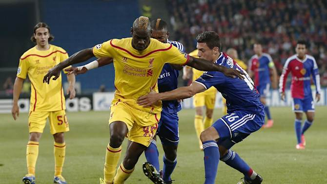 Liverpool's Mario Balotelli, left, fights for the ball against Basel's Geoffroy Serey Die, center, and Basel's Fabian Schaer, right,  during the Champions League group B soccer match between Real Madrid and PFC Ludogorets, at Vassil Levski stadium in Sofia, Bulgaria, Wednesday, Oct. 1, 2014. (AP Photo/Valentina Petrova)
