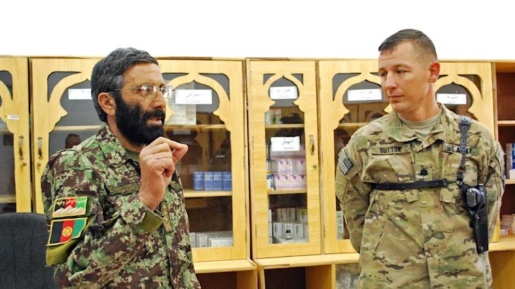 Afghan National Army Col. Shazad Gul speaks to American adviser Lt. Col. Thomas Sutton, of the 101st Airborne Division, on Saturday, May 26, 2013 at the medical clinic at Camp Parsa in Khost Province, Afghanistan. As Afghan forces take over fighting this year, the Afghan National Army is struggling with a shortage of doctors. (AP Photo/Kristin M. Hall)