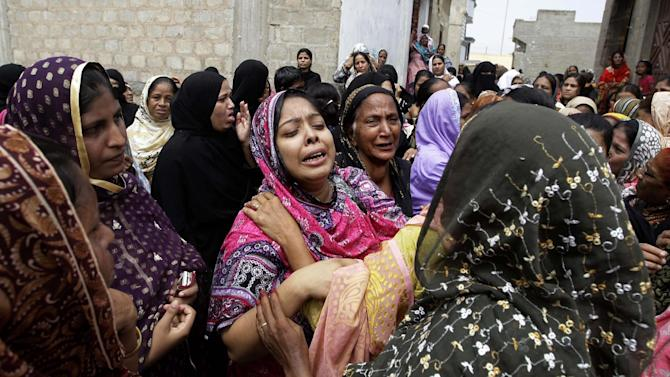 Pakistani women mourn the death of a relatives killed from a fire in a factory in Karachi, Pakistan, Thursday, Sept. 13, 2012. Pakistani police say they have registered a murder case against the owners and managers of a garment factory in the southern city of Karachi where a fire killed hundreds of people. (AP Photo/Fareed Khan)