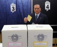 Former Prime Minister Silvio Berlusconi casts his vote at a polling station in Milan February 24, 2013. Italians began voting on Sunday in one of the most closely watched elections in years, with markets nervous about whether it can produce a strong government to pull Italy out of recession and help resolve the euro zone debt crisis. REUTERS/Stefano Rellandini
