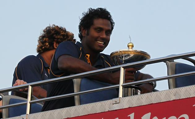 Sri Lankan cricket captain Angelo Mathews, right, smiles holding cup as he sits in an open bus with team mate Lasith Malinga, left, upon their return from Bangladesh after winning the Asia Cup in Colo