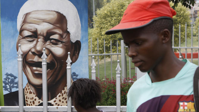 A child looks through a fence at a portrait of former president Nelson Mandela in a Park in Soweto, South Africa, Thursday, March, 28, 2013. 94-year-old Mandela, the anti-apartheid leader who became South Africa's first black president, has been hit by a lung infection again and is in a hospital, the presidency said. Mandela, has become increasingly frail in recent years and has been hospitalized several times in recent months, including earlier this month when he underwent what authorities said was a scheduled medical test. The Nobel laureate is a revered figure in South Africa, which has honored his legacy of reconciliation by naming buildings and other places after him and printing his image on national banknotes. (AP Photo/Denis Farrell)