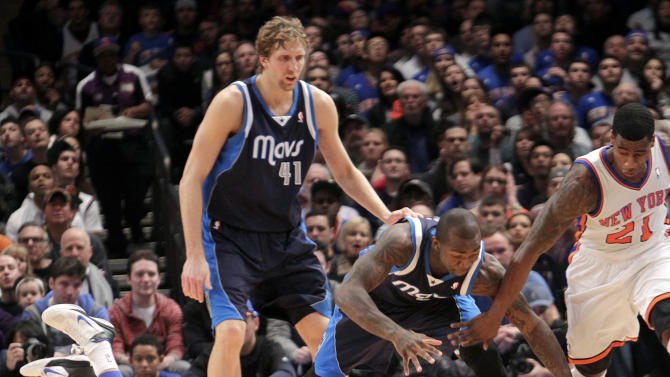 Dallas Mavericks' Dirk Nowitzki (41), top, and Dominique Jones, second from right, fight for a loose ball with New York Knicks' Iman Shumpert, right, and Jeremy Lin during the second half of an NBA basketball game in New York, Sunday, Feb. 19, 2012. The Knicks defeated the Mavericks 104-97. (AP Photo/Seth Wenig)