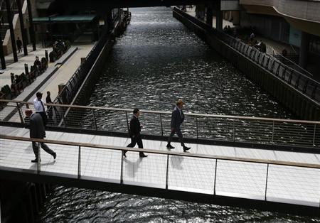City workers cross a bridge in Canary Wharf, east London