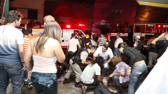 People help an injured man, victim of a fire in a club in Santa Maria city, Rio Grande do Sul state,  Brazil,  Sunday, Jan. 27,  2013.  According to police more than 200 died in the devastating nightclub fire in southern Brazil.  Officials say the fire broke out at the Kiss club in the city of Santa Maria while a band was performing. At least 200 people were also injured. (AP Photo/Agencia RBS)