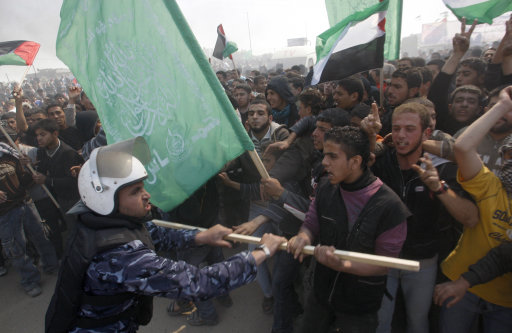 FILE - In this March 30, 2012 file photo, a Hamas security officer tries to prevent protesters from reaching Erez crossing during a march heading towards the border with Israel in the northern Gaza Strip. In a report released Wednesday. 3, 2012 international rights group Human Rights Watch says Hamas' security forces in Gaza are committing severe abuses, including torture of detainees, arrests without warrants, forced confessions, unfair trials and mock executions. (AP Photo/Hatem Moussa, File)