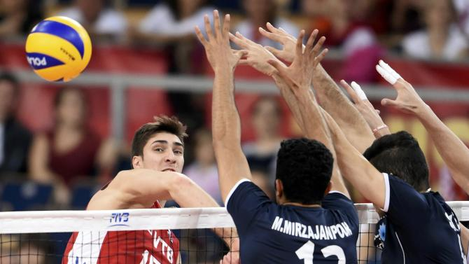 Russia's Ilinykh spikes the ball against Iran's Mirzajanpour M. and Mahmoudi during their match at the FIVB Volleyball Men's World Championship Poland 2014 at Atlas Arena  in Lodz