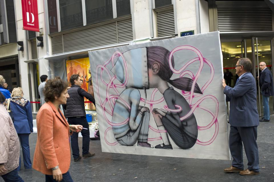 People hold a painting by French artist Seth outside Drouot auction house, in Paris, Thursday Oct. 24, 2013. This painting is one among dozens of art pieces from street artists which will be auctioned Friday Oct. 25. (AP Photo/Thibault Camus)