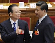 Chinese Premier Wen Jiabao (left) talks to Vice President Xi Jinping after a meeting at the Great Hall of the People in Beiijing on March 11 . Xi has made his first public appearance in two weeks, state media said, following swirling speculation about the whereabouts of Beijing's leader-in-waiting