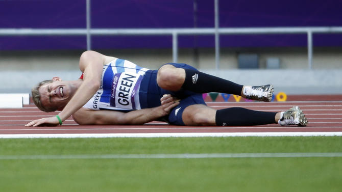 Britain's Jack Green holds his thigh after falling in a men's 400-meter hurdles heat during athletics competition in the Olympic Stadium at the 2012 Summer Olympics, Saturday, Aug. 4, 2012 in London. (AP Photo/Matt Dunham)