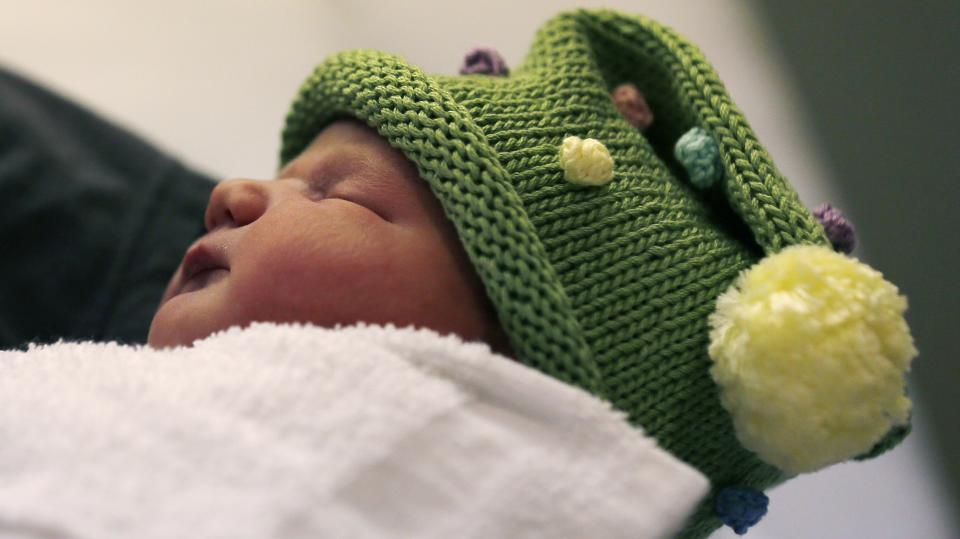 Newborn Noelle Joy Klinker, of Reading, Mass., who was born at 12:12 p.m. at the Massachusetts General Hospital, rests in her mother Colleen's arms a few hours after birth on Wednesday, Dec. 12, 2012 in Boston. Noelle was a natural birth. (AP Photo/Charles Krupa)