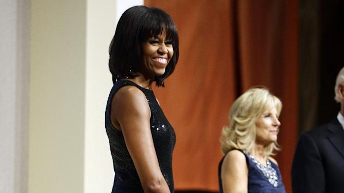 First lady Michelle Obama and Jill Biden are seen as President Barack Obama speaks to supporters and donors at an inaugural reception for the 57th Presidential Inauguration at The National Building Museum in Washington, Sunday, Jan. 20, 2013. (AP Photo/Charles Dharapak)
