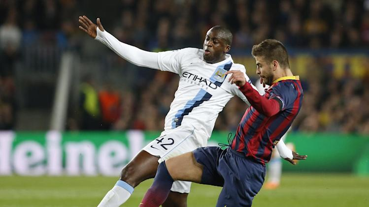 Manchester City's Yaya Toure, left is tackled by Barcelona's Gerard Pique during a Champions League, round of 16, second leg, soccer match between FC Barcelona and Manchester City at the Camp Nou Stadium in Barcelona, Spain, Wednesday March 12, 2014