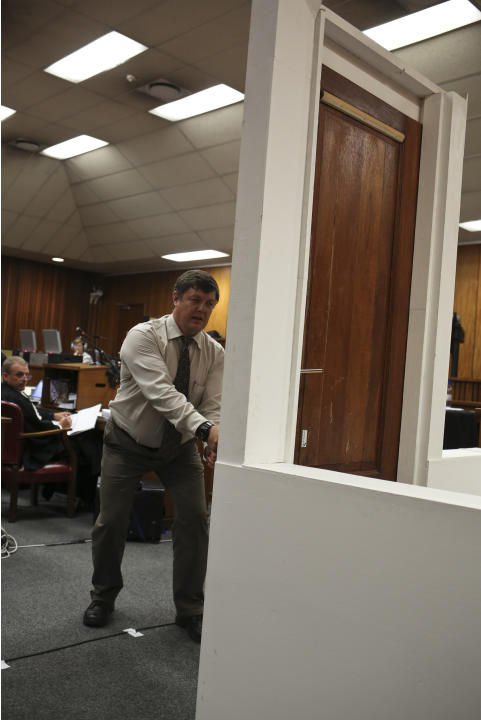 Forensic investigator Johannes Vermeulen, with a cricket bat in hand, demonstrates on a mock-up toilet and door details of how the door could have been broken down, during the trial of Oscar Pistorius