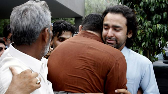 People comfort Musa Gilani, right, the brother of Ali Haider Gilani who has been kidnapped in Multan, Pakistan, Thursday, May 9, 2013. Gunmen attacked an election rally in Pakistan's southern Punjab province on Thursday and abducted Ali Haider Gilani son of a former prime minister, intensifying what has already been a violent run-up to Saturday's nationwide elections. (AP Photo/Zeeshan Hussain)